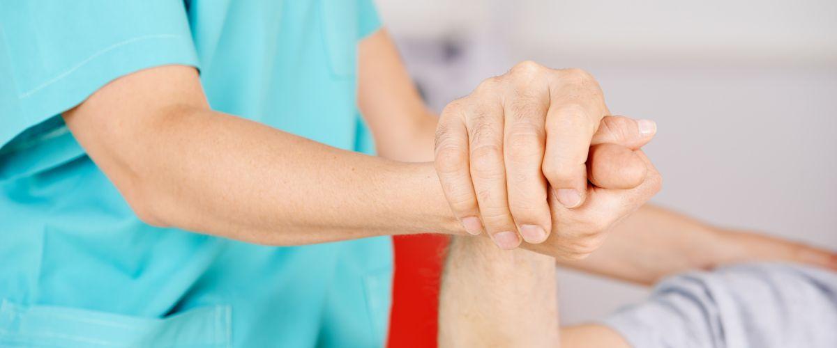 Krankenschwester hält Hand eines Senioren