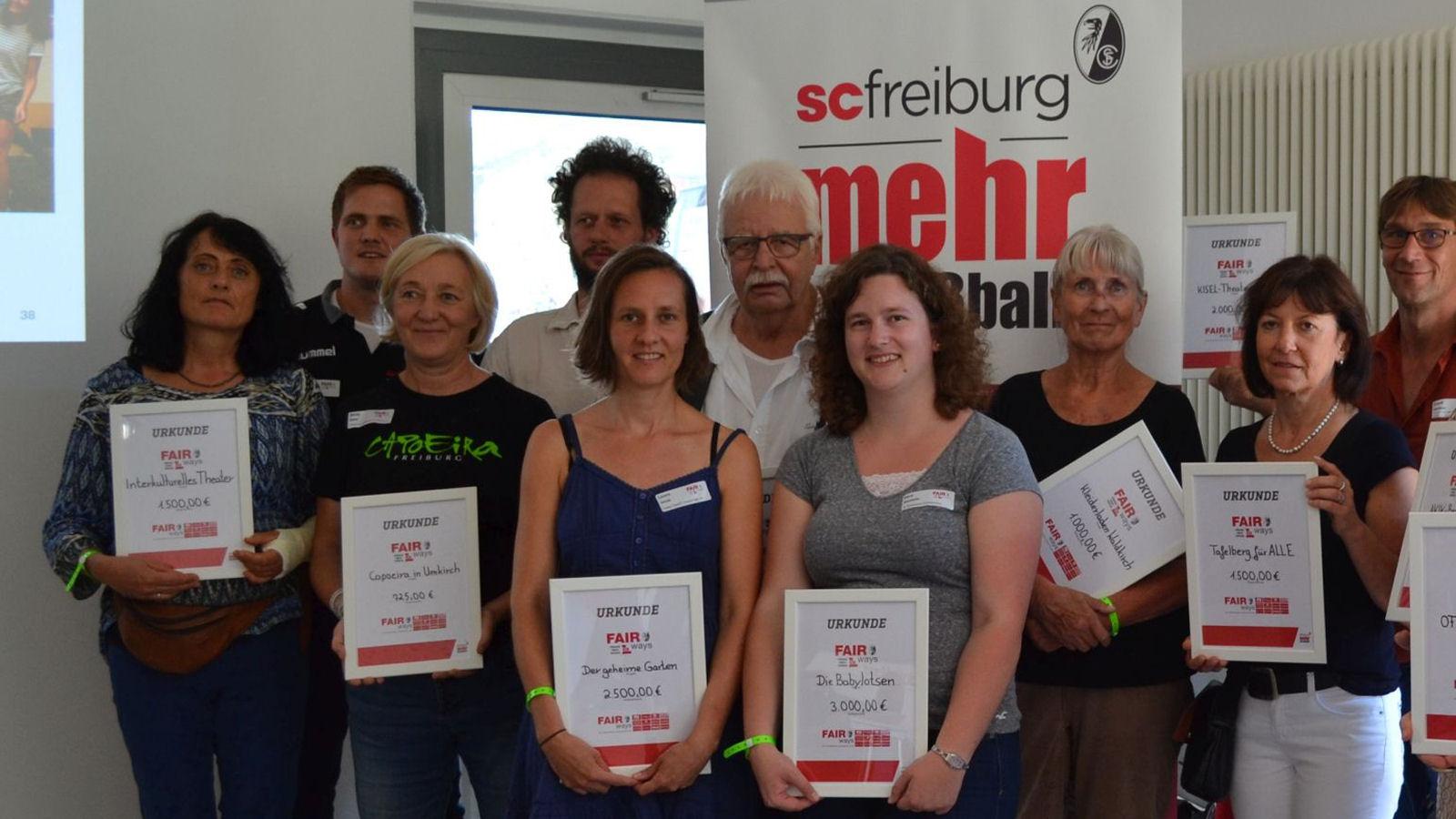 Babylotsin Vera Stächelin (1. Reihe, vierte von links) nimmt neben 25 weiteren Projektvertretern die Spende des SC Freiburg entgegen.