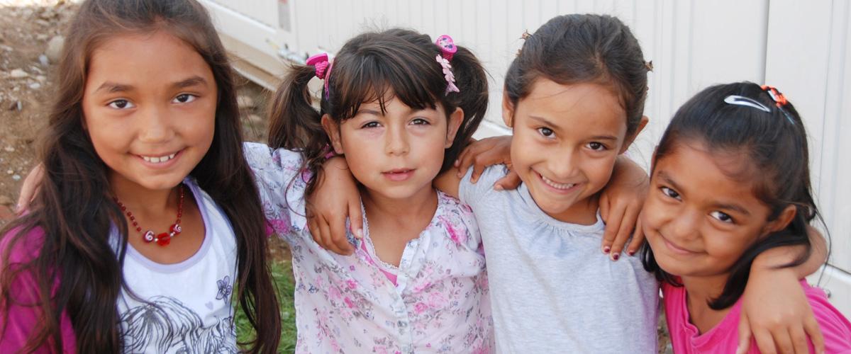 Flüchtlinge: Vier Mädchen halten sich im Arm und lachen
