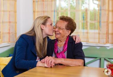 Ein Enkel besucht seine Großmutter. Umarmung und Küsschen
