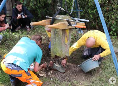 Der gebrochene Sandstein wird auf das im Boden einbetonierte Unterteil gesetzt. Fotoquelle: Landratsamt Lörrach, Fachbereich Vermessung & Geoinformation