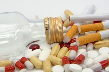 Suchtmittel wie Tabletten, Zigaretten und Alkohol liegen auf einem Tisch