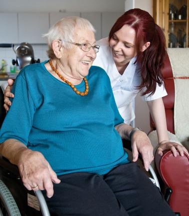 Ambulanter Dienst im Pflegeheim Schloss Rheinweilder; eine Mitarbeiterin kümmert sich um eine Bewohnerin im Rollstuhl