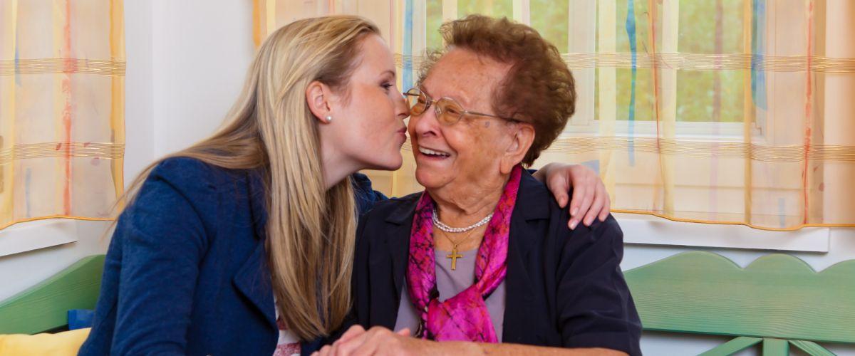 Tochter gibt der Mutter einen Kuss auf die Wange