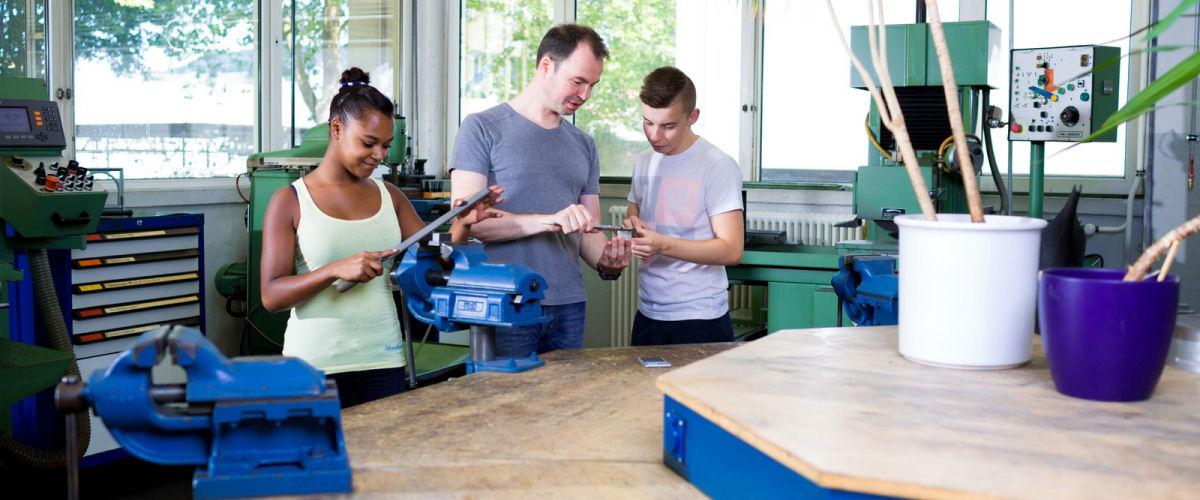 In den Beruflichen Schulen bringt ein Lehrer zwei Schülern die Metallverarbeitung näher.