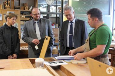 Herr Eiche (r.) erklärt Landrätin Dammann, Martin Dalhoff und Schulpräsident Rudolf Bosch (v.l.) wie er für die jungen Flüchtlinge den Unterricht in Holzverarbeitung gestaltet