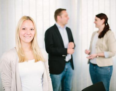 Eine blonde junge Frau lächelt, während sich im Hintergrund zwei Kollegen unterhalten