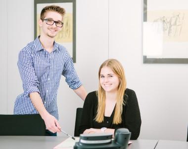 Ein junger Mann steht neben einer jungen Frau, die an einem Schreibtisch sitzt. Beide lächeln.