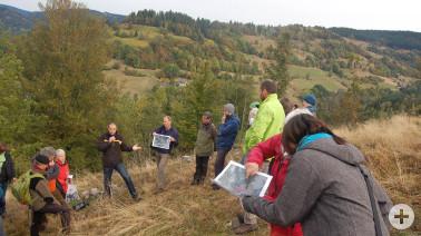"""Tilmann König (mit Mikrofon) liefert den Teilnehmenden Informationen zum Weidfeld """"Windfeld"""" und Bürgermeister a. D. Bernhard Seger zeigt die Fläche auf der Gebietskarte."""