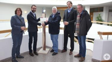 Erster Landesbeamter Ulrich Hoehler (links) überreicht Studiendirektor Peter Zwickel sein Preisgeld vor der kunstvollen Holzstele, die den Pokal des European Energy Awards trägt.
