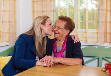 Ein Enkel besucht seine Großmutter. Umarmung und Küsschen.