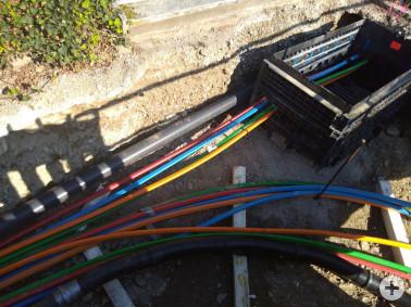 Farbenfroh: Glasfaserleerrohrbündel nebeneinander im Graben (in Bad Bellingen). Das rote Bündel gehört zum überörtlichen Backbonenetz, die anderen Farben zu innerörtlichen Verteilnetzen.
