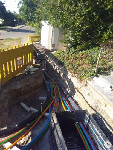Frisch verlegte Glasfaserleerrohre im offenen Graben mit Kabelschacht (in Bad Bellingen)