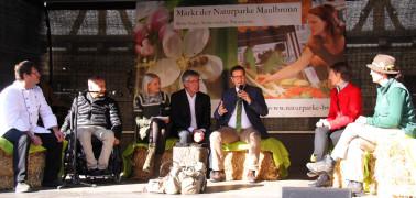 Im Gespräch auf der Marktbühne (v. l. n. r.): Naturpark-Wirt Georg Barta, Hans-Peter Matt (mahp-barrierefrei), Moderatorin Daniela Hilpp, Präsident Friedel Heuwinkel, Verband Deutscher Naturparke (VDN), Landwirtschaftsminister Peter Hauk MdL, Landrätin Ma