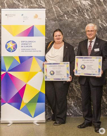 Sonya Baron (Leiterin der Stabsstelle für grenzüberschreitende Zusammenarbeit, Landkreis Lörrach) und Oberbürgermeister Wolfgang Dietz (Stadt Weil am Rhein) bei der Preisübergabe am 28.11.2018 in Berlin