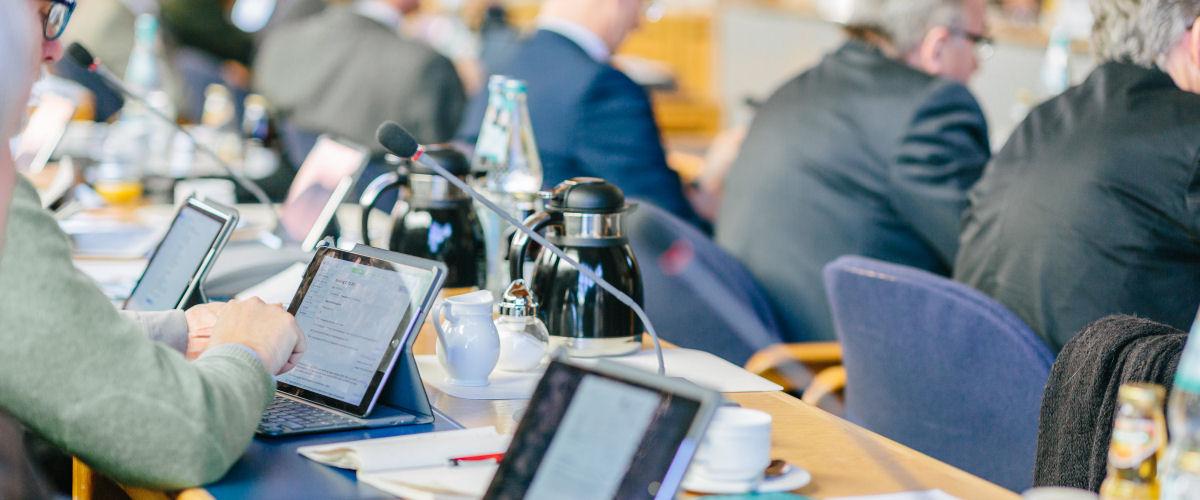 Kreisräte rufen während einer Kreistagssitzung die Unterlagen über das iPad auf.