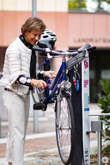 Landrätin Marion Dammann testet die Funktionen der neuen Radservice-Station vor dem Landratsamt.